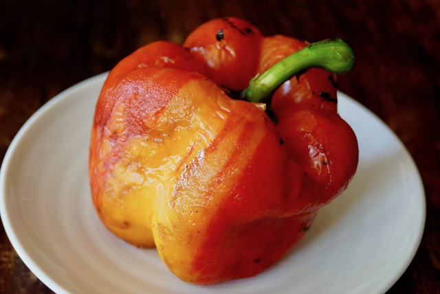 One whole roasted Enjoya pepper with stem on white plate.