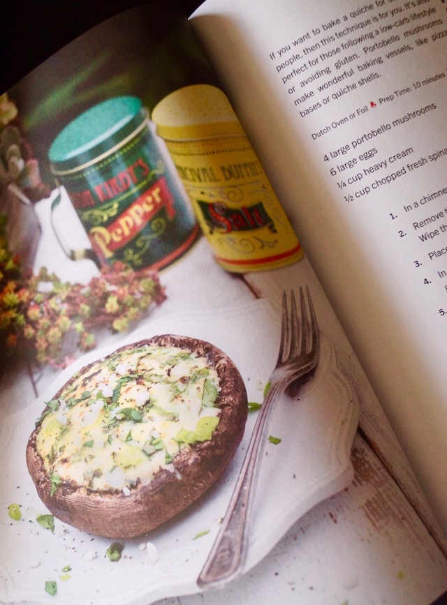 A page in Laura Bashar's Camp & Cabin Cookbook, with an image of a quiche cooked in a portabello shell.