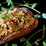 Mexican Poblano Rice Pliaf in a wooden, oval-shpaed bowl with cilantro sprigs on black background.