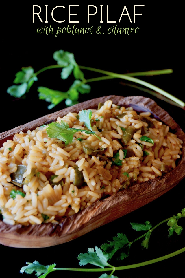 Mexican Poblano Rice Pliaf in a wooden, oval-shpaed bowl with cilantro sprigs.