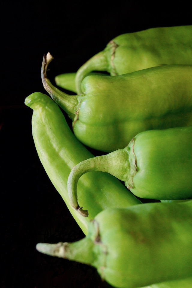 Bundle of bright green Hatch Chiles with black background.