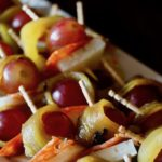 Roasted Hatch Chiles wrapped around red grapes with slices of Chorizo and cheese, with toothpicks.