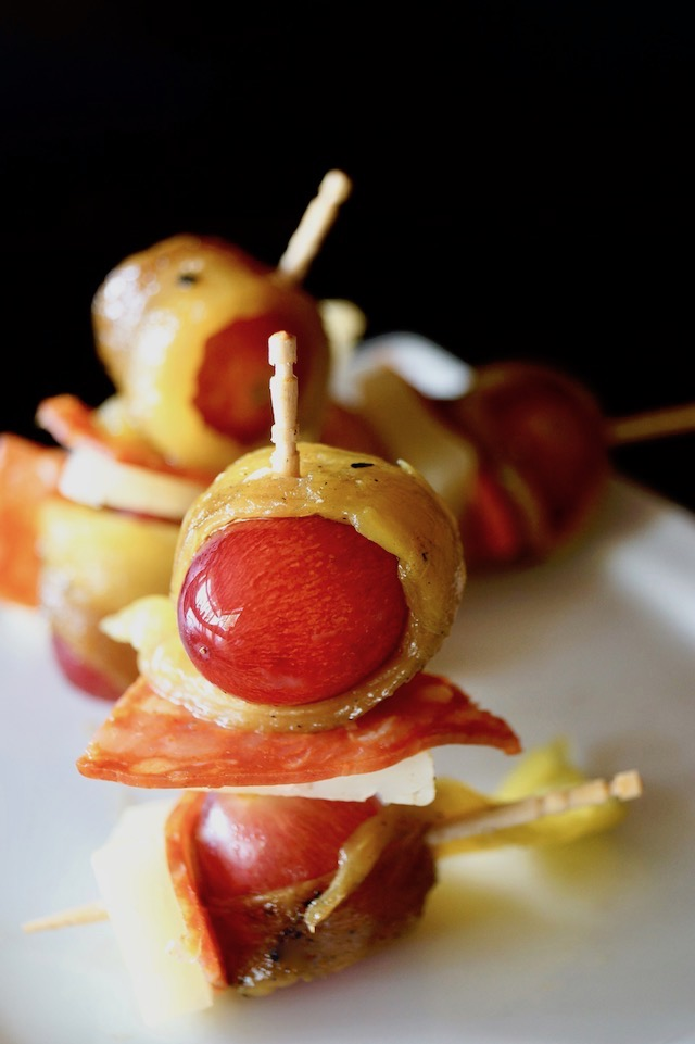 Roasted Hatch Chile wrapped around a red grape with a slice of Chorizo and cheese, all on a toothpick.