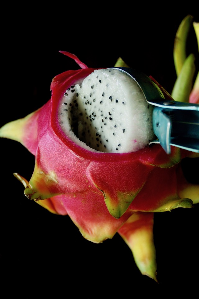 Dragon fruit being scoope out of skin with an ice cream scooper