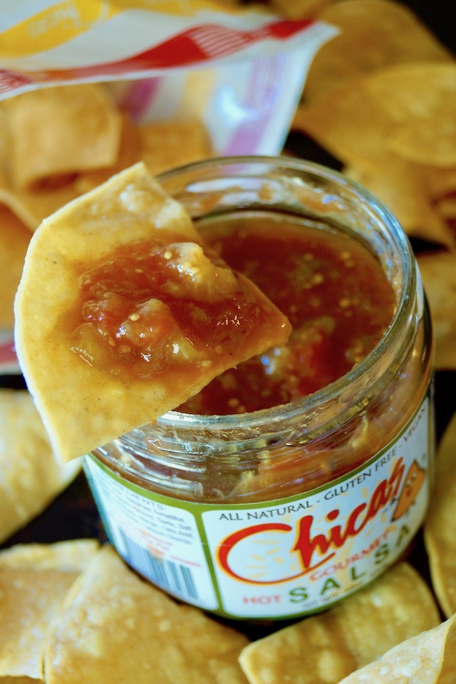 Jar of Chicas Salsa with a chip with salsa on it, on top.