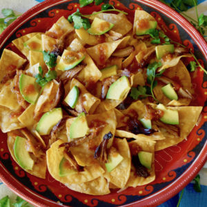Red plate full with Spiced Pulled Pork Nachos with avocado slices.