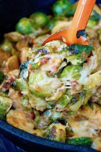 Cheesy Pancetta Brussels Sprouts Bake being spooned out of cast iron skillet with an orange spoon.