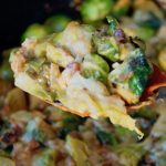 Cheesy Pancetta Brussels Sprouts Bake with a spoonful held above a cast iron skillet with an orange spoon.