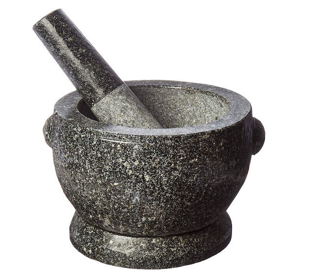 Dark gray granite mortar and pestle on white background.