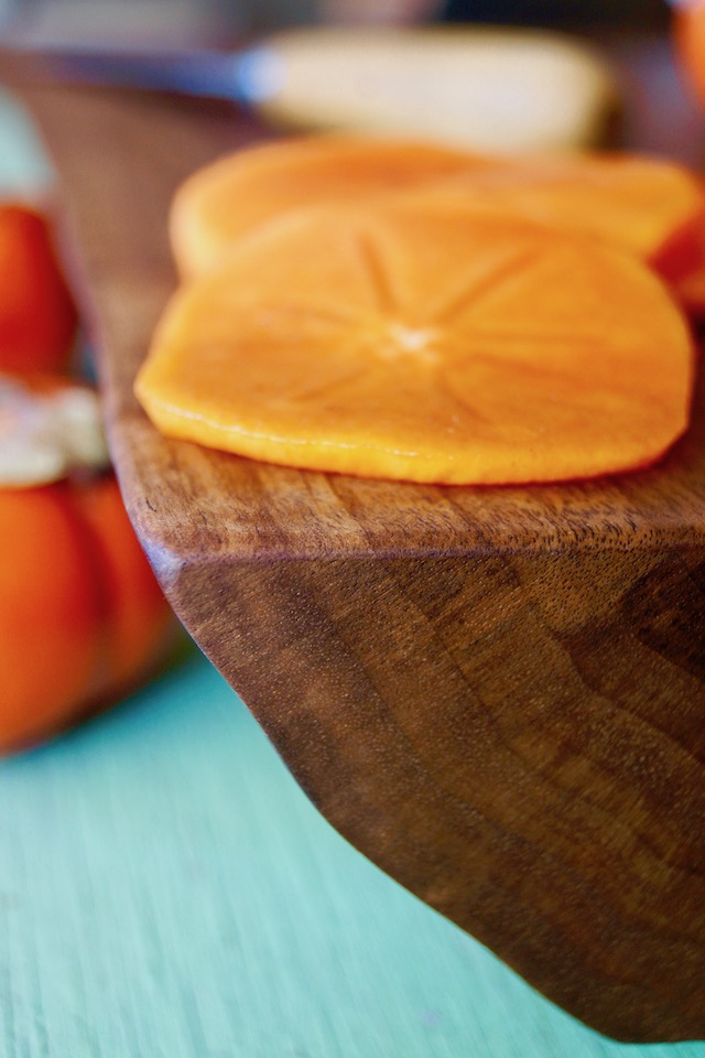 Corner edge of cutting board with persimmon slices.