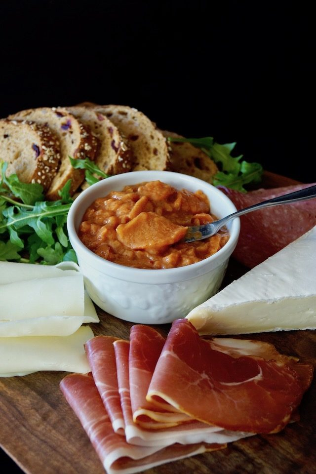 Spicy Persimmon Preserves in a white bowl surrounded by meats, cheeses and bread slices