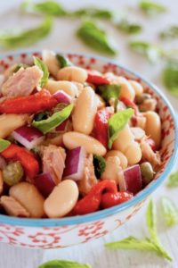 Cannelllini Bean Tuan Salad i a white bowl with blue trim and red flowers on it.