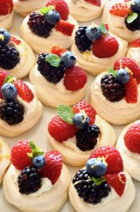 Close up a several Mini Lemon Berry Pavlovas on parchment paper
