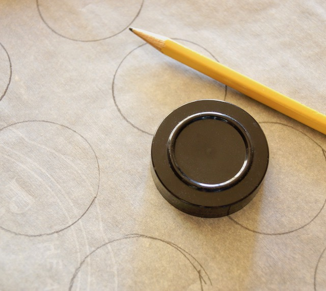 parchment paper with pencil and small black lid to trace for meringue bases for Pavlova