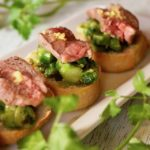 Asparagus Aussie Lamb Crostini on a white plate with fresh parsley.