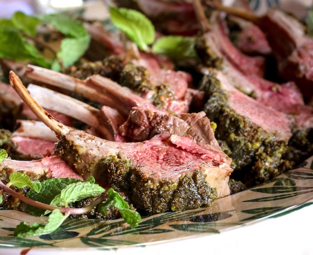 Several Pistachio Mint Cursted Lamb Chops on a platter with fresh mint