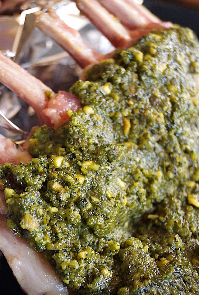 Raw rack of lamb with pistachio mint pesto spread over it