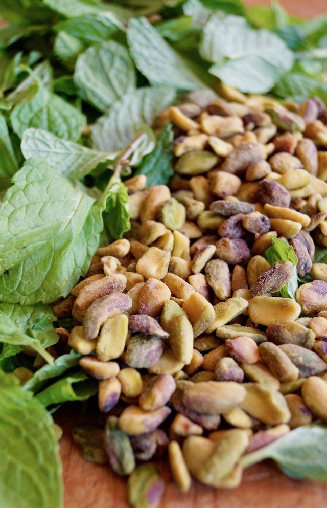 Fresh mint and toasted pistachio nuts on cutting board
