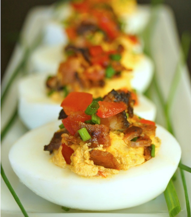 Chipotle-Bacon Deviled Eggs on a narrow white platter with fresh chives