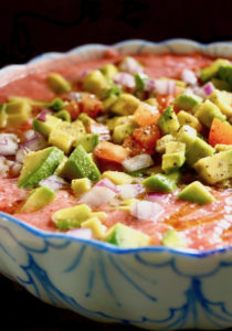 Easy Tomato Gazpacho recipe in a blue and white bowl with diced aocados, tomatoes and onion on top