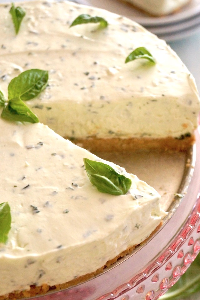 Basil Cheesecake with one slice removed, on pink platter