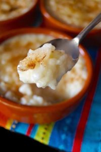 Arroz con Leche in teracotta ramekin with one bite held in the air in spoon