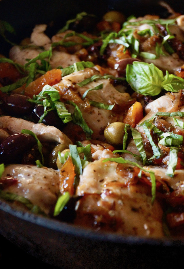 Skillet Chicken Thighs with Apricots and Oilves in cast iron pan with basil on top