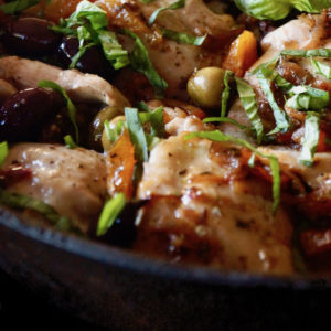 Close up of Skillet Chicken Thighs with Apricots and Oilves in cast iron pan with basil