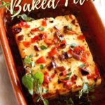 Close up of Baked Feta with Olives and Roasted Peppers with fresh oregano in a terra cotta dish with title text