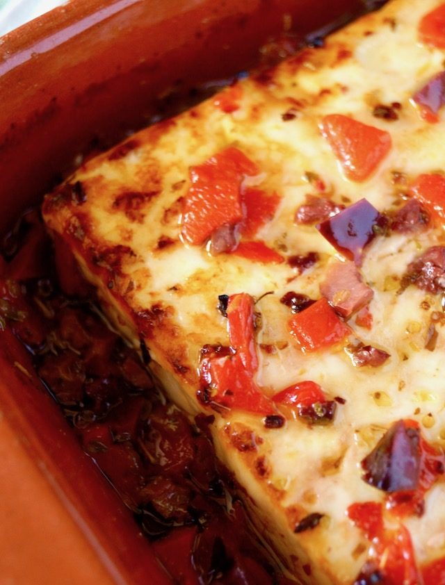 close up of a golden-topped baked feta in terra cotta dish