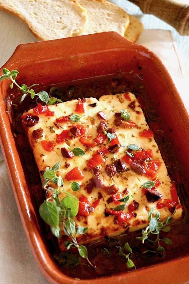 Baked Feta with Olives and Roasted Peppers with fresh oregano in a terra cotta dish