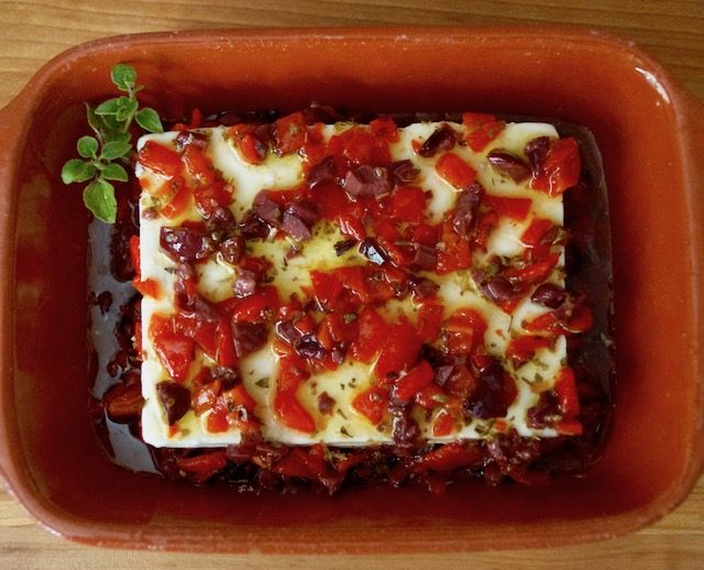 Feta in oil with olives and peppers in terra cotta dish