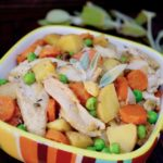 Crustless Chicken Pot Pie in colorful striped bowl with fresh sage leaaves