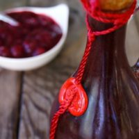 Balsamic Cranberry Dressing in a tall bottle with a cork.