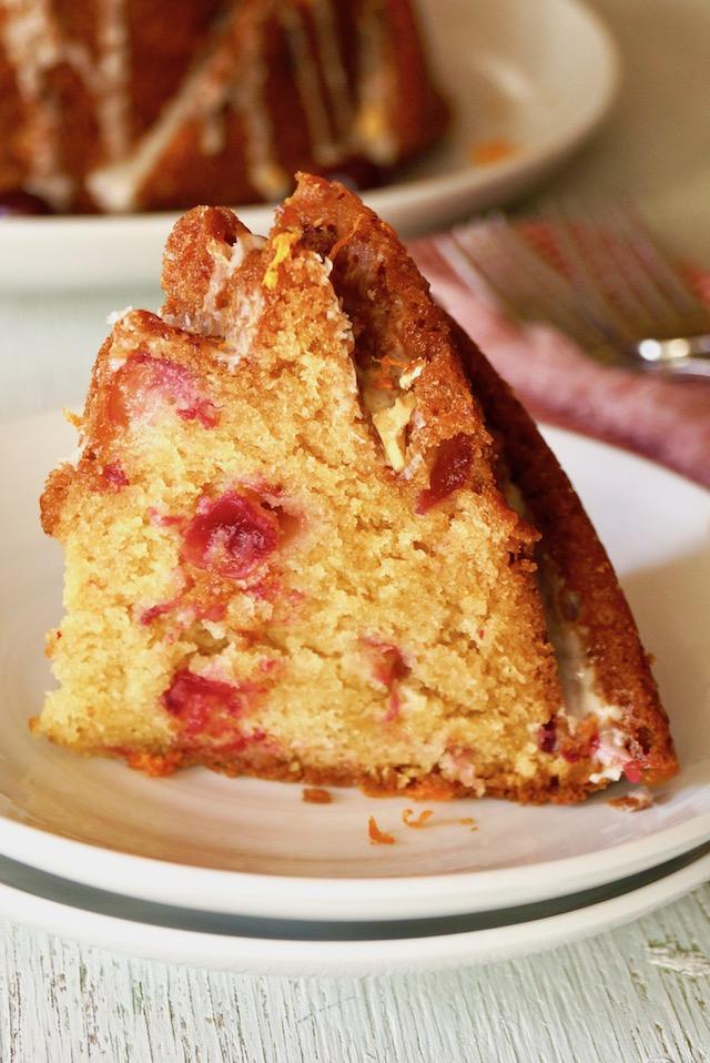 big slice of cranberry orange cake with amaretto glaze on white plate