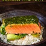 Fillet of cilantro chimichurri baked salmon on rice in black bowl