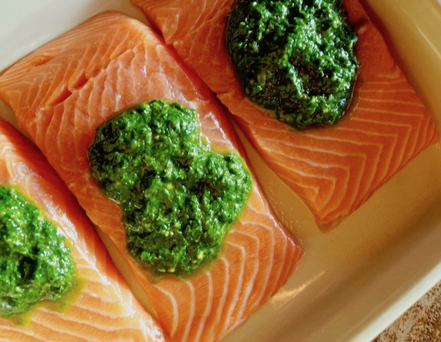 three raw salmon fillets with dollops of chimichurri on thme