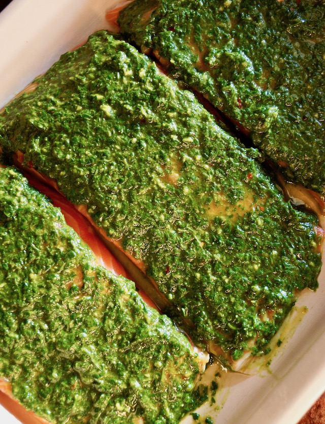 Three raw fillets of salmon with chimichurri spread over them