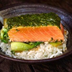 Fillet of Cilantro Chimichurri Salmon on rice in black bowl