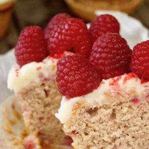 Raspberry cupcake cut in half with raspberries on top