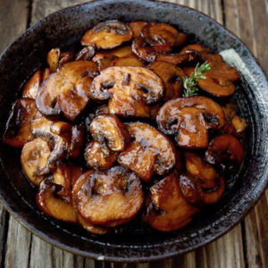close up of browned mushroom slices in a black bowl