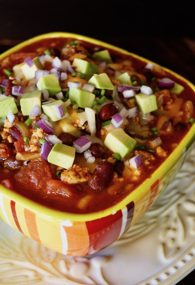 Striped colorful bowl with Vegetarian Tofu Chili with avocado on top