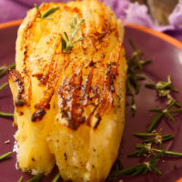 thick slice of potato pave on purple plate with rosemary