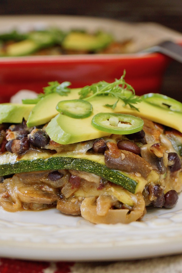 One serving of Grilled Zucchini Casserole on white plate with avocado on top