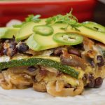 Close up of one serving of Grilled Zucchini Casserole on white plate with avocado on top