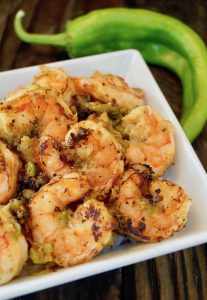 Hatch Green Chile Shrimp in white bowl with green hatch behind it