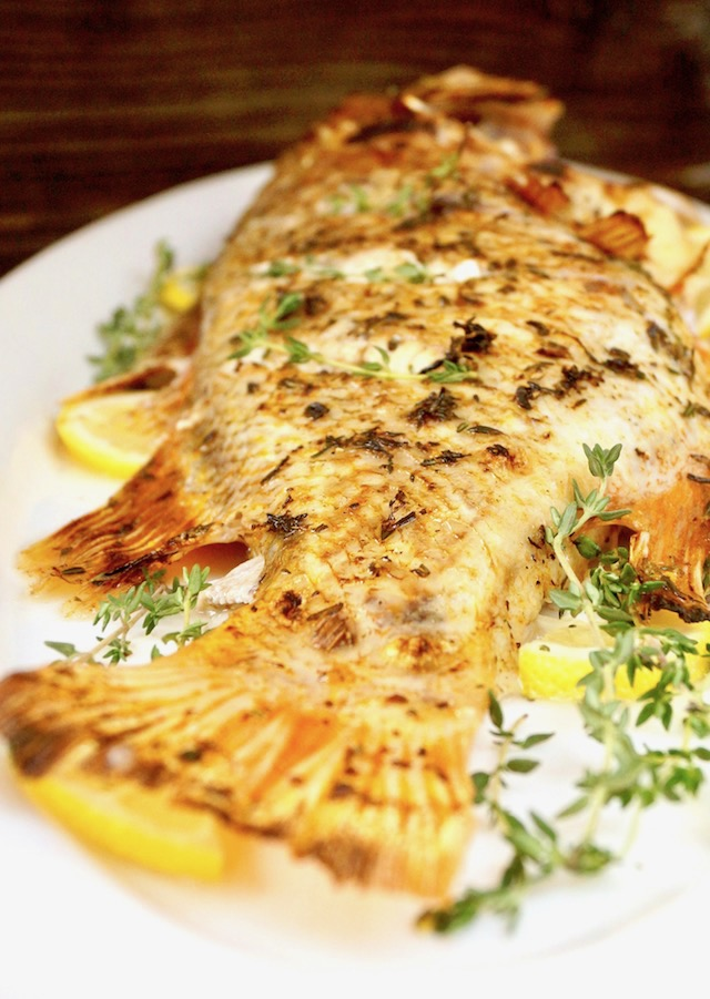 whole baked rockfish recipe with fresh thyme and lemon on white platter