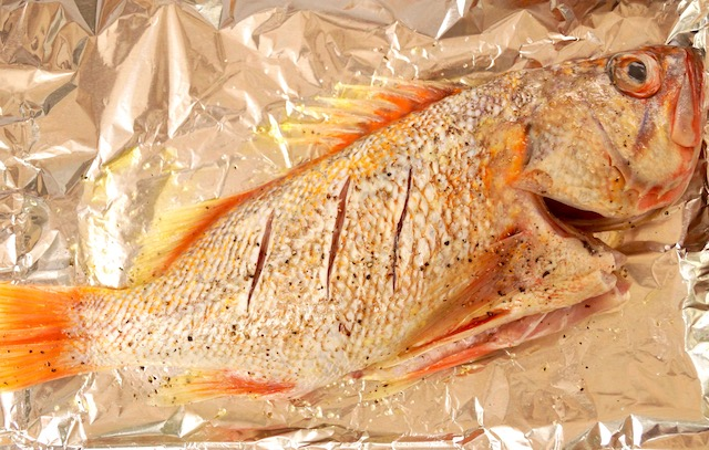 whole raw rockfish with three slits cut on surface on foil
