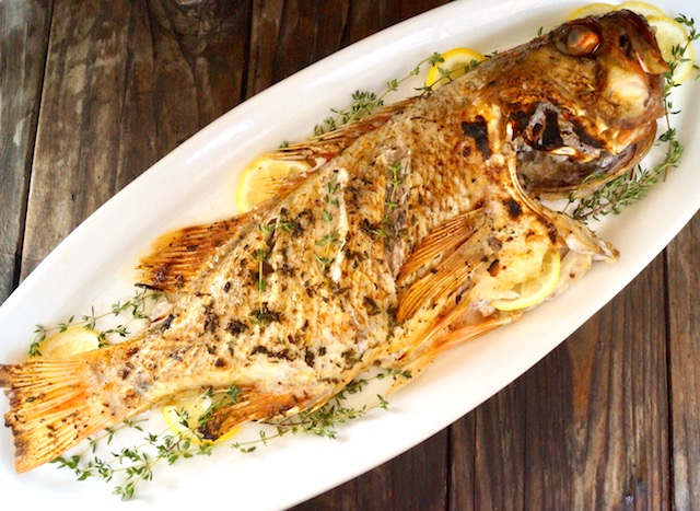 Whole Baked Vermilion Rockfish withlemon and thyme on white platter