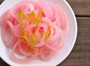 Pickled Shallots with lime zest on top on white plate